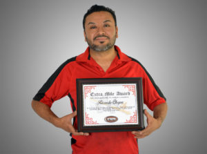 Ricardo Chapa Holding His Extra Mile Award